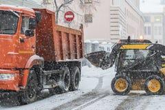 Nieve de la carga del excavador en el camión calles de vaciamiento de la nieve b foto de archivo