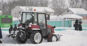 Nieve de la limpieza del tractor en el día Nevado del invierno en ciudad Vehículo del servicio del invierno en trabajo Vehículo d almacen de metraje de vídeo
