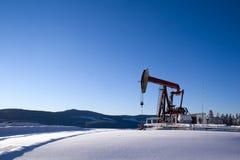 Nieve de la montaña del pumpjack del pozo de petróleo Imagen de archivo