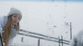Nieve de limpieza al aire libre de la muchacha en su parabrisas del coche Vista desde adentro del coche metrajes