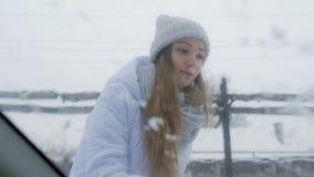 Nieve de limpieza al aire libre de la muchacha en su parabrisas del coche Vista desde adentro del coche almacen de video