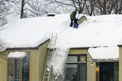 Nieve de vaciamiento de un tejado en Quebec fotografía de archivo libre de regalías