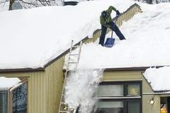 Nieve de vaciamiento de un tejado en Quebec fotografía de archivo
