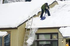 Nieve de vaciamiento de un tejado en Quebec foto de archivo
