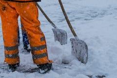 Nieve del barrido de los trabajadores del camino en invierno Imágenes de archivo libres de regalías