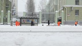 Nieve del barrido de los trabajadores de la acera en invierno, acera de limpieza de la tormenta de la nieve metrajes