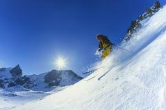 Nieve del polvo del esquí del hombre joven en montañas en invierno Foto de archivo