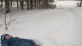 Nieve del soplo del muchacho del adolescente de las manos en la madera Forest Park del invierno El boe caucásico cayó abajo almacen de metraje de vídeo
