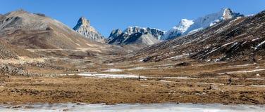 Nieve del witn de las montañas y abajo con los turistas en la tierra con la hierba marrón, la nieve y la charca congelada en invi Fotos de archivo libres de regalías