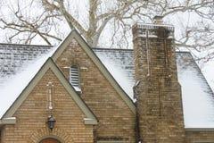 Nieve en el tejado con la chimenea del hogar histórico del ladrillo amarillo con el árbol de abedul en el fondo Imagenes de archivo