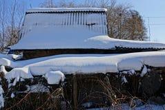 Nieve en el tejado de pizarra de un granero rural en la yarda fotografía de archivo