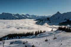 Nieve en el top de las montañas y de la niebla abajo del valle foto de archivo