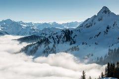 Nieve en el top de las montañas y de la niebla abajo del valle imagen de archivo