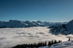 Nieve en el top de las montañas y de la niebla abajo del valle imágenes de archivo libres de regalías