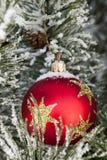 Nieve en la chuchería roja de la Navidad Fotos de archivo libres de regalías