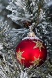 Nieve en la chuchería roja de la Navidad Imagenes de archivo