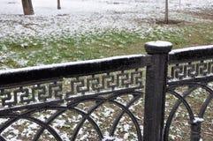 Nieve en una cerca en un parque de la primavera Fotos de archivo