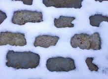 Nieve entre las piedras del adoquín Fotos de archivo