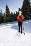 Nieve femenina Skiier que se inclina en postes y la sonrisa Imágenes de archivo libres de regalías