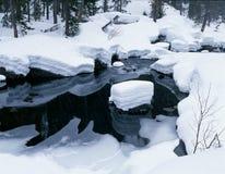 Nieve a lo largo del río y de reflexiones negras del agua Fotografía de archivo