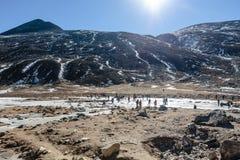 Nieve negra del witn de la montaña y abajo con los turistas en la tierra con la hierba marrón, la nieve y la charca congelada en  Imagen de archivo