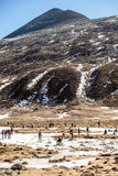Nieve negra del witn de la montaña y abajo con los turistas en la tierra con la hierba marrón, la nieve y la charca congelada en  Foto de archivo