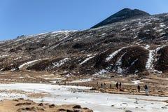 Nieve negra del witn de la montaña y abajo con los turistas en la tierra con la hierba marrón, la nieve y la charca congelada en  Imagenes de archivo