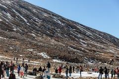 Nieve negra del witn de la montaña y abajo con los turistas en la tierra con la hierba marrón, la nieve y la charca congelada en  Fotos de archivo libres de regalías