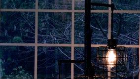 Nieve que brilla intensamente en ventana de la noche hacia fuera con la luz caliente de la lámpara almacen de video