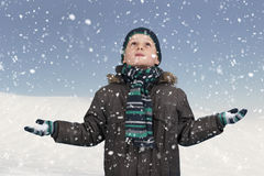 Nieve que cae abajo en el muchacho que mira para arriba Fotos de archivo libres de regalías