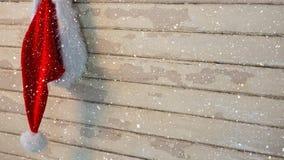 Nieve que cae con el sombrero de Papá Noel de la Navidad en la madera