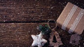 Nieve que cae con las decoraciones de la Navidad y regalo en la madera