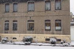Nieve que cae delante de una casa urbana urbana Foto de archivo libre de regalías