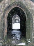Nieve que cae en las ruinas de la entrada de la iglesia del heptonstall foto de archivo