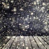 Nieve que cae en un fondo negro con la tabla de madera vacía para nosotros Imagen de archivo libre de regalías