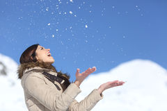 Nieve que lanza de la mujer feliz en el aire en holdays del invierno Imagen de archivo libre de regalías