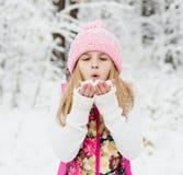 Nieve que sopla de la chica joven Foto de archivo libre de regalías