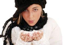 Nieve que sopla de la muchacha adolescente de las manos Foto de archivo libre de regalías