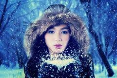 Nieve que sopla de la muchacha bastante asiática en la cámara Fotos de archivo