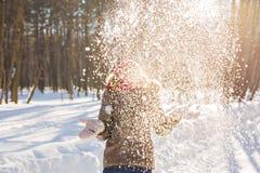 Nieve que sopla de la muchacha de la belleza en parque escarchado del invierno outdoors Copos de nieve del vuelo Fotografía de archivo libre de regalías