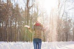 Nieve que sopla de la muchacha de la belleza en parque escarchado del invierno outdoors Copos de nieve del vuelo Imagenes de archivo