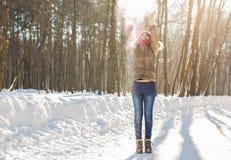 Nieve que sopla de la muchacha de la belleza en parque escarchado del invierno outdoors Copos de nieve del vuelo Foto de archivo