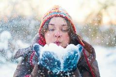 Nieve que sopla de la muchacha del invierno de la belleza en parque escarchado Imagenes de archivo