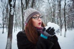 Nieve que sopla de la muchacha del invierno de la belleza en parque escarchado del invierno Fotos de archivo libres de regalías
