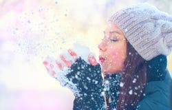 Nieve que sopla de la muchacha del invierno en parque escarchado del invierno Fotos de archivo