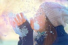 Nieve que sopla de la muchacha del invierno en parque escarchado del invierno Imagen de archivo