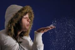 Nieve que sopla de la mujer femenina Fotos de archivo libres de regalías