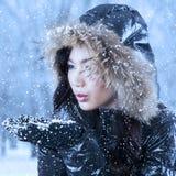 Nieve que sopla de la mujer joven en las manos Imagenes de archivo