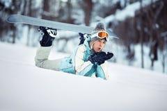 Nieve que sopla del snowboarder de sexo femenino Imagenes de archivo