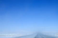 Nieve que sopla en la carretera Fotos de archivo libres de regalías